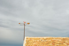 Rooftop weather vane. A weather vane against stormy cloudy sky royalty free stock photo