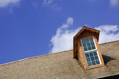 Rooftop Window. Angle rooftop with window and blue sky background stock photo
