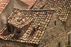 Rooftops in Dubrovnik. Old red tile rooftops in Dubrovnik are uneven and show interesting character. These roofs show some patching after the city was shelled in Royalty Free Stock Photography
