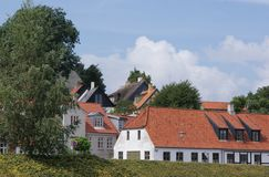 Rooftops of homes. Red tile and thatched roofs of buildings in Denmark and Europe with hedgerows Royalty Free Stock Photo
