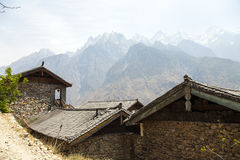 Rooftops and Mountain Peaks. The snow capped Jade Dragon Snow Mountain with Chinese stale rooftops in Yunnan Province, China Royalty Free Stock Photo