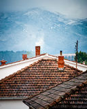 Rooftops with smoking chimneys in winter. Rooftops with smoking chimneys and snowy hills in the back Royalty Free Stock Photos