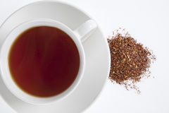 Rooibos Herbal Tea. Rooibos tea (asphalatis linearis) as an infusion and in dry state on white background Royalty Free Stock Photo