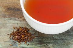 Rooibos red tea. A white cup of drink and loose leaves on wood background, tea made from the South African red bush, naturally caffeine free Stock Photography