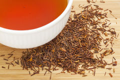 Rooibos red tea. A white cup of drink and loose leaves on bamboo wood background, tea made from the South African red bush, naturally caffeine free Royalty Free Stock Photography