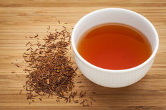Rooibos red tea. A white cup of a drink and loose leaves on bamboo wood background, tea made from the South African red bush, naturally caffeine free Royalty Free Stock Photography