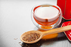 Rooibos in spoon closeup, two tea cups and tea tin box on table Royalty Free Stock Photos