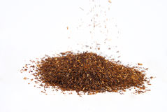 Rooibos tea. Heap of Rooibos tea, with some granules falling Stock Images