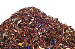 Rooibos tea. A pile of rooibos tea mixed with dry fruits and herbs on a white background Royalty Free Stock Image