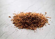 Rooibos tea. Dry fermented  leaves on black slate surface Stock Photography