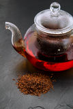 Rooibos tea. Dry leaves and a small glass teapot brewing, on black slate surface Royalty Free Stock Photos