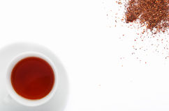 Rooibos tea and leaves. Cup of south african rooibos tea, healthy non caffeine detoxing drink with loose scattered leaves Stock Images