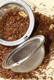 Rooibos tea with tea strainer Royalty Free Stock Photos