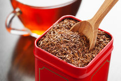 Rooibos in tea tin box closeup. Rooibos in tea tin box and wooden spoon closeup Royalty Free Stock Photography