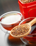 Rooibos in wooden spoon closeup, two tea cups and tea tin box Royalty Free Stock Image