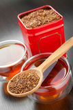 Rooibos in wooden spoon, two tea cups and tea tin box Stock Photo