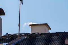 Rook die uit de schoorsteen van een huis komen Stock Foto's