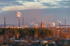 Rook van industriële pijpen op de rand van de stad stock fotografie