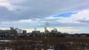 Rook van installatie tegen de blauwe hemel met wolken De winterlandschap met gedeeltelijk snow-covered gebied stock videobeelden