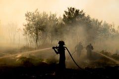 Rookgebied en brandweerman na wildfire sihouette Stock Afbeelding