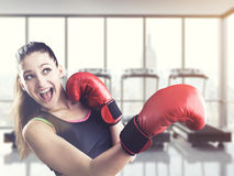 Rookie boxer in a gym. Rookie woman boxer making a punch in gym with treadmills. Concept of competitive sports. Toned image Royalty Free Stock Photo