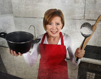 Rookie home cook woman in red apron at home kitchen holding cooking pan and rolling pin crying sad in stress Stock Photos