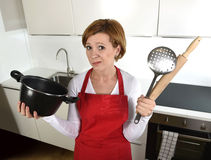 Rookie home cook woman in red apron at home kitchen holding cooking pan and rolling pin sad in stress confused and helpless Royalty Free Stock Photo