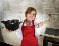 Rookie home cook woman in red apron at home kitchen holding cooking pan and rolling pin sad in stress confused and helpless. Young attractive rookie home cook Stock Photo