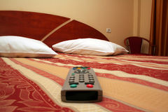 Room. Luxury hotel room decor accommodation with TV remote in front plane royalty free stock photos