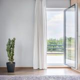 Room with balcony idea. Light room with open balcony doors, cactus in pot standing on the floor stock photos
