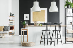 Room with bar stools. White lamps above kitchen countertop with bar stools and braided pouf on wall in room with gold painting stock images