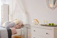 Room with bed with canopy. Mirror and white dresser stock image