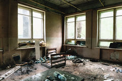 Room with big windows and furniture in old ruined abandoned building Royalty Free Stock Photo