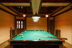 Room billiards decorated in dark wood with low lamps, billiard table with green cloth royalty free stock photo