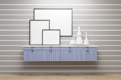 Room with blue drawers and posters, gray wall. Gallery with blue set of drawers and vases standing on it. There are three posters on a gray wall with white Stock Image
