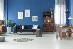 Room with blue wall. Spacious retro style living room with blue wall and wooden floor royalty free stock image