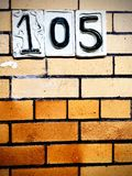 Room 105. Brick wall with number plate 105 stock photos