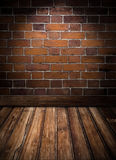 Room with brick wall and wooden floor Stock Images