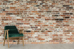 Room with brick wall. Wooden green armchair in the room with red brick wall stock photography