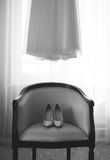 Room of bride, wedding shoes on chair and dress Stock Photography