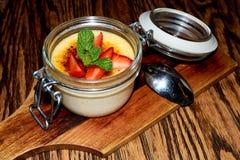 Room brulle dessert in de glaskruik met een aardbei en muntbovenste laagje stock foto's