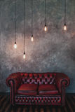 Room with a concrete wall and marsala leather sofa. Loft interior lights.  Stock Photography