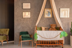 Room with crib, chairs and drawings. Baby room with wooden crib, green chairs and drawing on grey wall stock photography