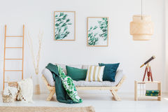 Room with dark green accents. Telescope on wooden table in living room with dark green accents and paintings with floral motif Royalty Free Stock Images