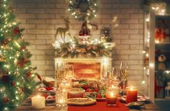 Room decorated for Christmas. Merry Christmas and Happy New Year! A beautiful living room decorated for holidays. Table served to the dinner stock image