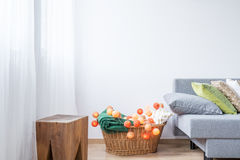 Room with decorative cotton balls. Bright room with decorative, orange cotton balls and grey sofa Stock Photography