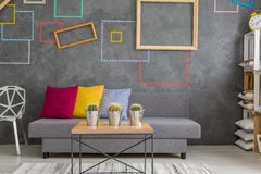 Room with decorative wall squares. Trendy living room with decorative wall squares and grey sofa royalty free stock photo
