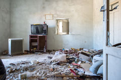 Room destroyed with furniture and old television Stock Photography