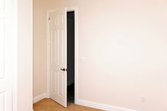 Room with door ajar. A white door is slightly open beside a big blank wall with copy space Stock Photography