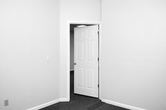 Room door opening out. Black and white image of an empty room with door opening out royalty free stock image